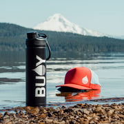 BUOY Brand Logo Transfer Sticker on a coffee mug with a floating hat in the background at Timothy Lake, Oregon - BUOY WEAR