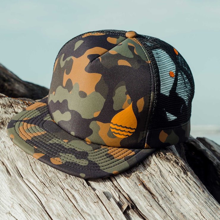 Camo Floating, Waterproof Trucker Hat with Snapback on a large piece of driftwood on the beach with the ocean and sky in the background - BUOY WEAR