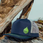 Navy Limited Edition Floating, Waterproof Trucker Hat with Snapback on some driftwood with the sky in the background - BUOY WEAR