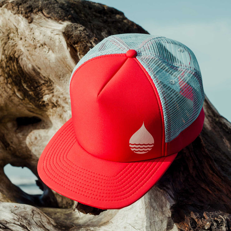Red Floating, Waterproof Trucker Hat with Snapback hanging on a large piece of driftwood on the beach with the ocean waves and sky in the background - BUOY WEAR