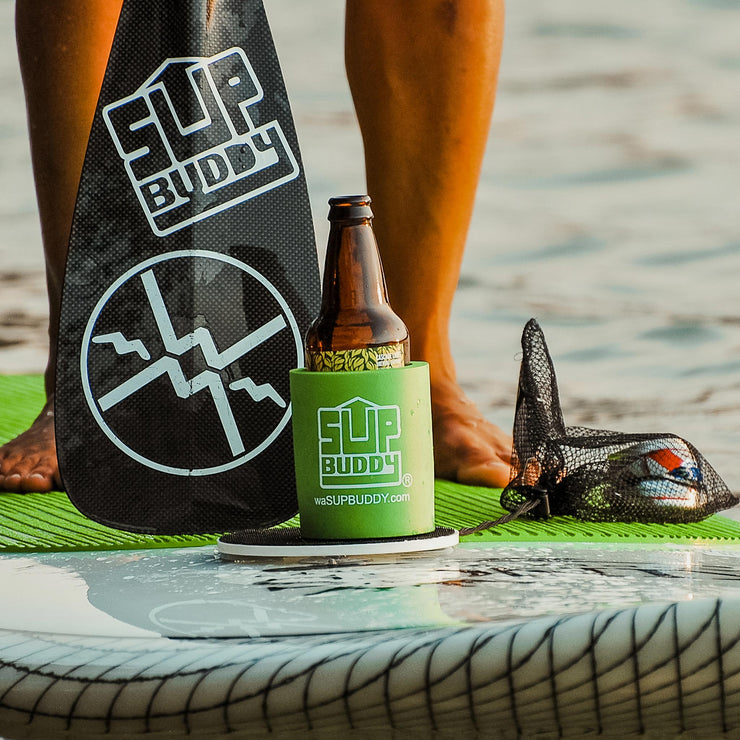 Zoomed in photo of a green SUPBUDDY Koozie on a Stand Up Paddleboard on the beach - BUOY WEAR