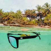 KZ Gear Floating, Polarized Sunglasses floating in the ocean with palm trees in the background - BUOY WEAR