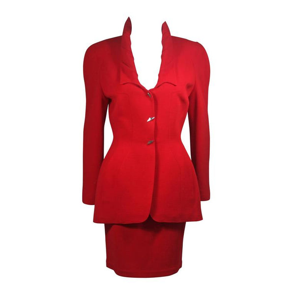 This skirt suit is composed of red fabric. The jacket has center front closures with silver hardware. The skirt has a classic pencil silhouette with zipper closure. In excellent vintage condition. Made in France.