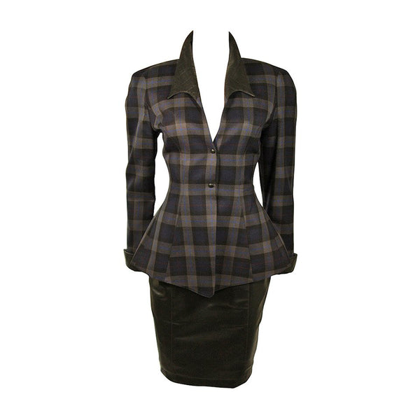 This Thierry Mugler two-piece skirt suit is composed of a blue and grey plaid with faux leather. The jacket is accented by a quilted faux leather at the collar and cuffs. The skirt is composed of a black faux leather and features a pencil silhouette with zipper at the center back. This garment is excellent for design purposes, the collar is deteriorating (See photos). Made in France.