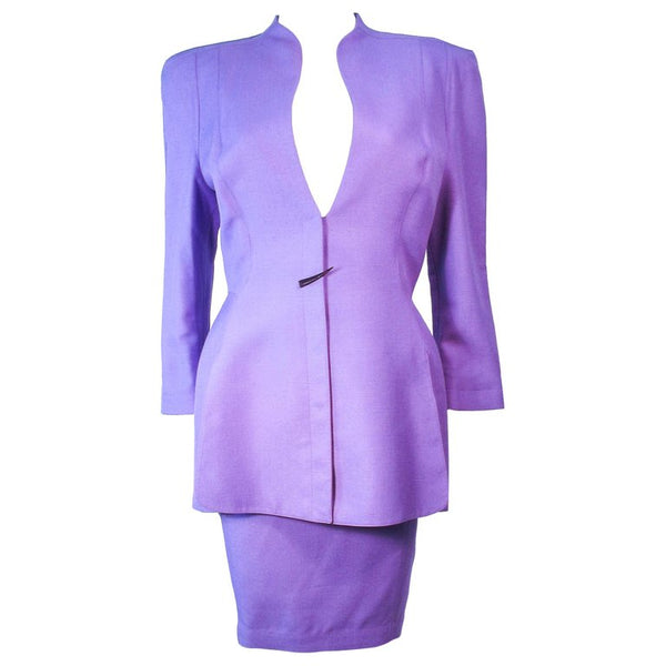 This Thierry Mugler skirt suit is composed of a lavender/purple hue fabric. Features a classic Mugler silhouette with nipped waist and curved bust-line to neckline design. The classic pencil style skirt features a zipper closure. In good vintage pre-owned condition (some signs of wear due to age) the skirt shows signs of alterations. Made in France.