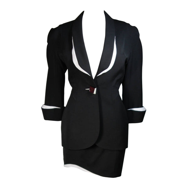 This fabulous Thierry Mugler ensemble is comprised of medium weight wool gabardine with a dramatic sculpted white lapel and cuff detail in white satin. Fitted waist has a single Tri-color abstract square button echoing the white edges of the lapels and cuffs. Medium density shoulder pads. Fitted skirt with a hidden zipper and covered satin snap at back with 3-D white detail at the hem.