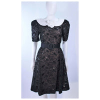 ARNOLD SCAASI Belle De Jour Black Sequin Lace Cocktail Dress Size 10. This Arnold Scaasi cocktail dress is composed of black lace with sequin embellishment. Features a center back zipper closure and contrast white collar with puff sleeves. In excellent vintage condition.