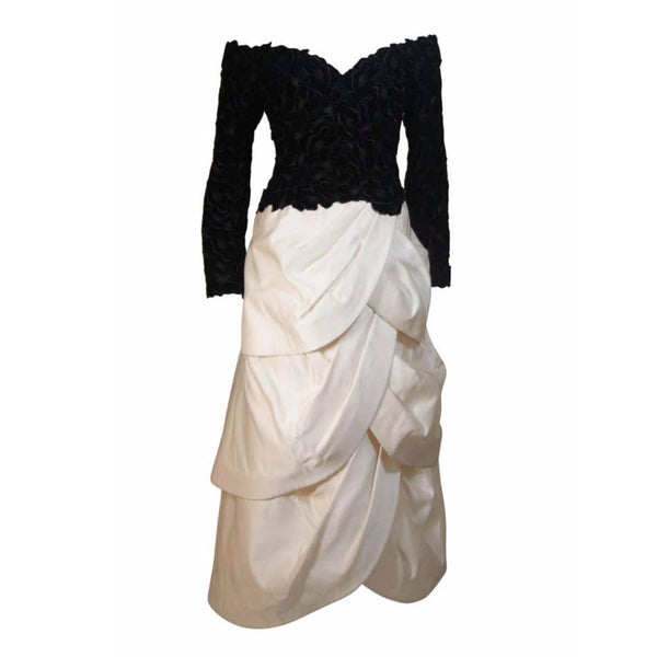This Arnold Scaasi Couture gown is composed of a black velvet bodice fabricated from floral cut-outs and an off white tiered silk satin skirt. The gown has an off the shoulder style design with sweetheart neckline. There is a center back zipper closure and zippers at the sleeve end. In excellent vintage condition.