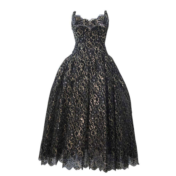 This Scaasi gown is composed of a black and gold floral patterned lace. The gown bodice features an exaggerated scalloped edge and the full skirt is layered for volume (also shot with additional crinoline). There is a center back zipper and boned foundation. In excellent vintage condition.