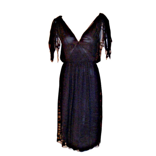 This is a navy blue three layer chiffon swirl print cocktail dress by Christian Dior Haute Couture, from the early 1980's. The dress has a deep v in the front and the back, knots at the top of each shoulder, and a side zipper with snaps. Provenance Betsy Bloomingdale