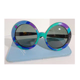EMILIO PUCCI Round Print Sunglasses w/ Case. These Emilio Pucci round plastic sunglasses feature a classic blue, green, and purple print. The lenses are black. They come with a baby blue leather case. Made in France. Measurements in Inches: Width: 6.5 Height: 3Length: 5.5