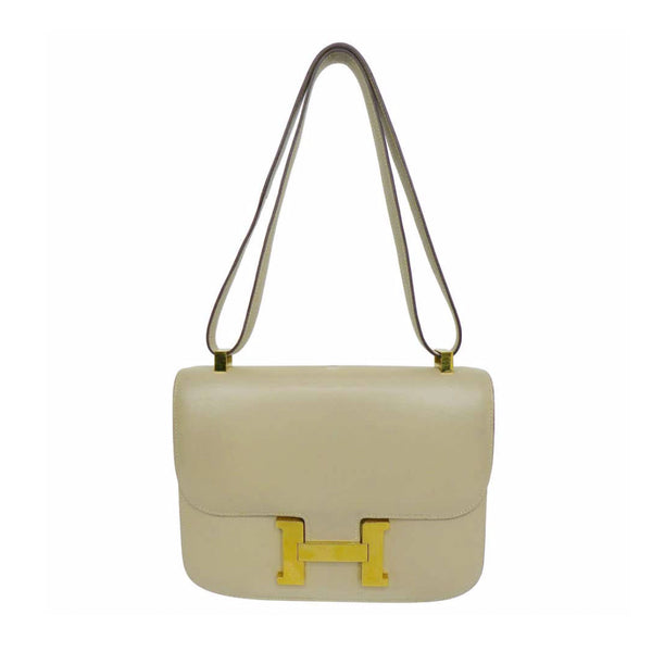 HERMES Camel Constance Crossbody Bag. This Hermes leather bag features a gold H closure, gold hardware, and a bone top stitch. Made in France. Measurements in Inches: Length: 9 Height: 7 Width: 2 Strap single: 32 Strap doubled: 19