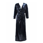 This Oleg Cassini is composed of a sequined black jersey. Features a draped front with center back zipper closure. In excellent vintage condition.