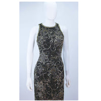 This Oleg Cassini gown is composed of a black silk with gold, black, and silver beading. Features a racer style neckline with center back zipper closure. In great vintage condition.