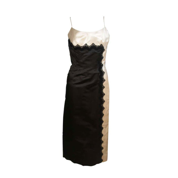 This Oleg Cassini cocktail dress is composed of black and off-white silk with lace applique. There is a center back zipper closure. and spaghetti strap. In excellent vintage condition.