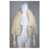 This Oleg Cassini jacket is composed of an off-white/cream hue mink. Features large rhinestone and faux pearl buttons. In excellent vintage condition, the lining does have some discoloration due to age.