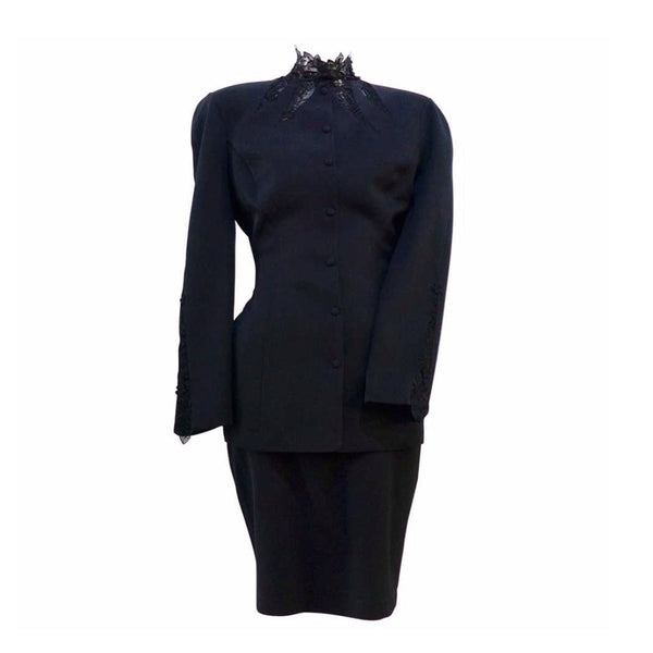 This THIERRY MUGLER skirt suit is composed of a black polyester and lace fabric. Features a classic Mugler silhouette with nipped waist and curved bust-line to neckline design. The jacket has front snap closures, rounded shoulders, and lace panels at the neck, back, and sleeves. The classic pencil style skirt features a zipper closure. In good vintage pre-owned condition. Made in France.Measurements in Inches:JacketBust: 38 Waist: 30 SkirtWaist: 27Hip: 38Length: 22