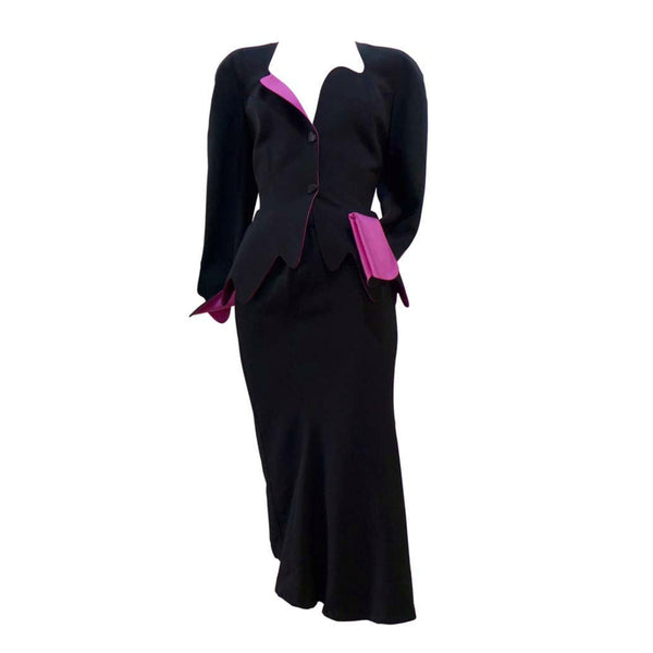 THIERRY MUGLER Black with Pink Lining and Cuff Skirt Suit Size 40. This THIERRY MUGLER skirt suit is composed of a black wool fabric with bright pink lining and cuff. Features a classic Mugler silhouette with nipped waist and curved bust-line to neckline design. The jacket has front snap closures, rounded shoulders, and a scalloped hem. The skirt features a zipper closure, flounce shape, and midi-length. In good vintage pre-owned condition. Made in France.Measurements in Inches:JacketBust: 40 Waist: 29 Skir