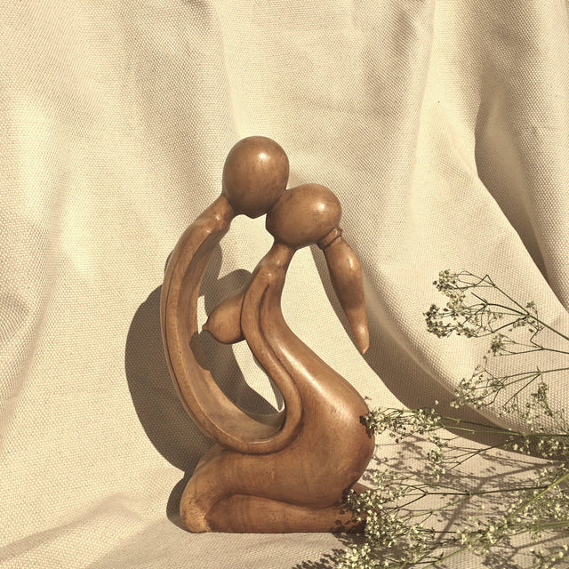 small wooden sculpture of a couple