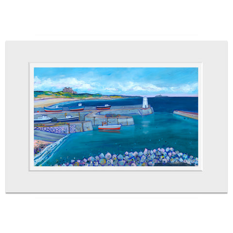 A mounted print of a scene of Seahorses harbour with colourful red boats and Bamburgh Castle and beach in the distance.