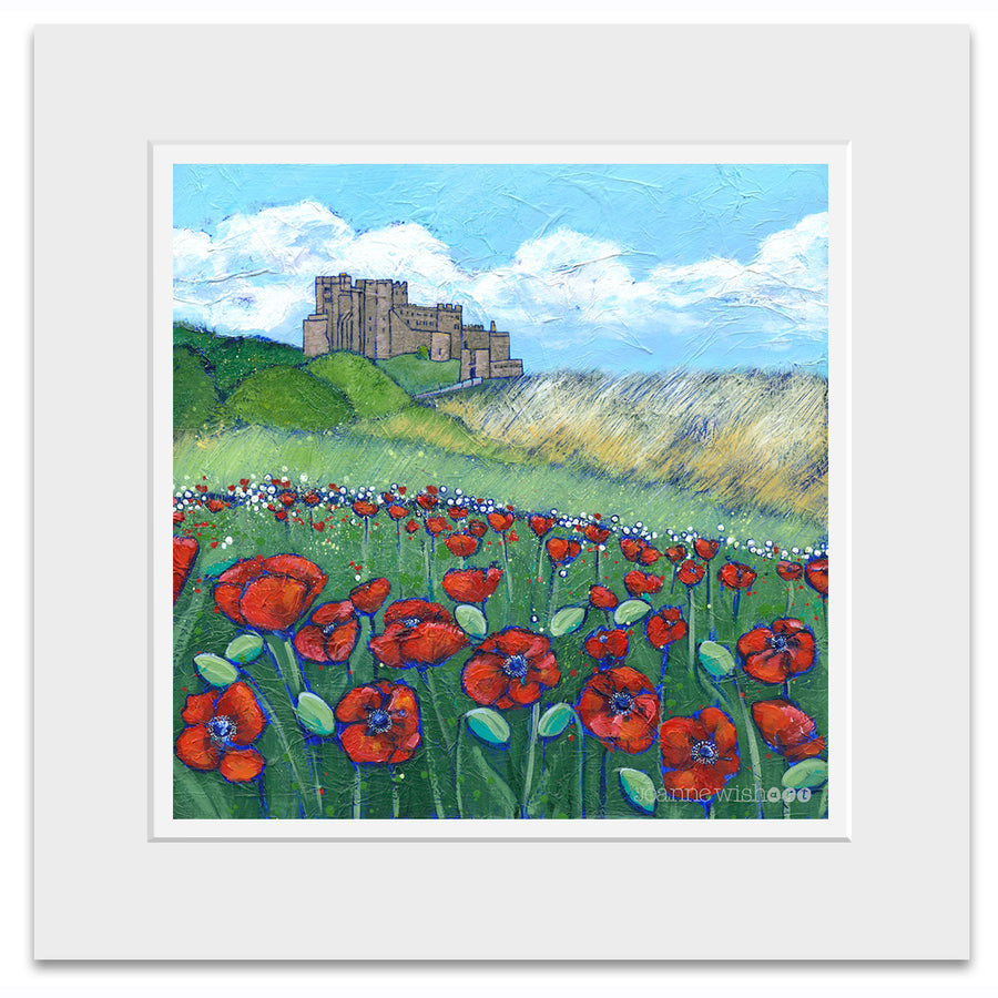 A mounted print of bamburgh castle with a swathe of bright red poppies in the dunes .