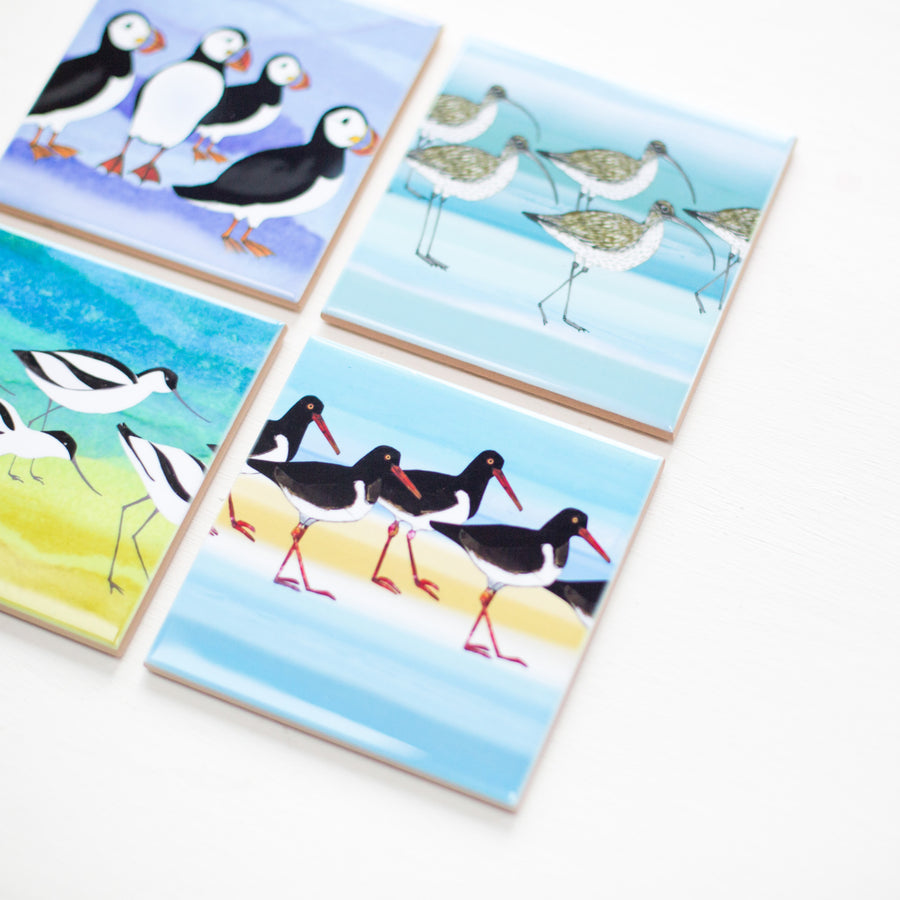 A close up look at one ceramic coaster featuring an oystercatcher.