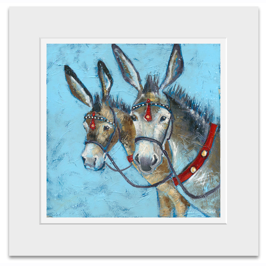 A mounted print of two seaside donkey heads with their ears pricked.
