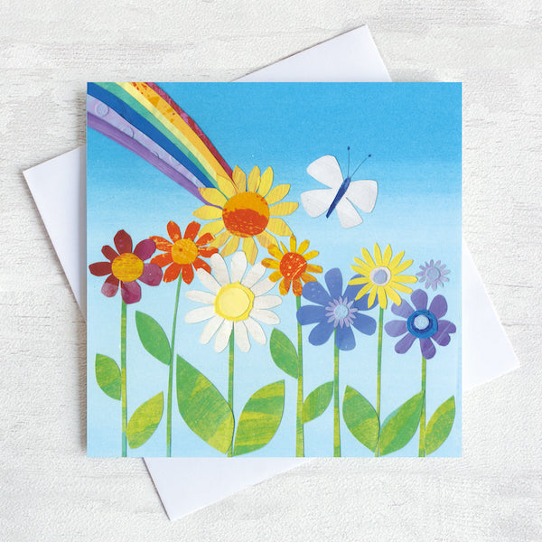 A Greetings Card featuring bright retro flowers with a rainbow bursting out from behind.