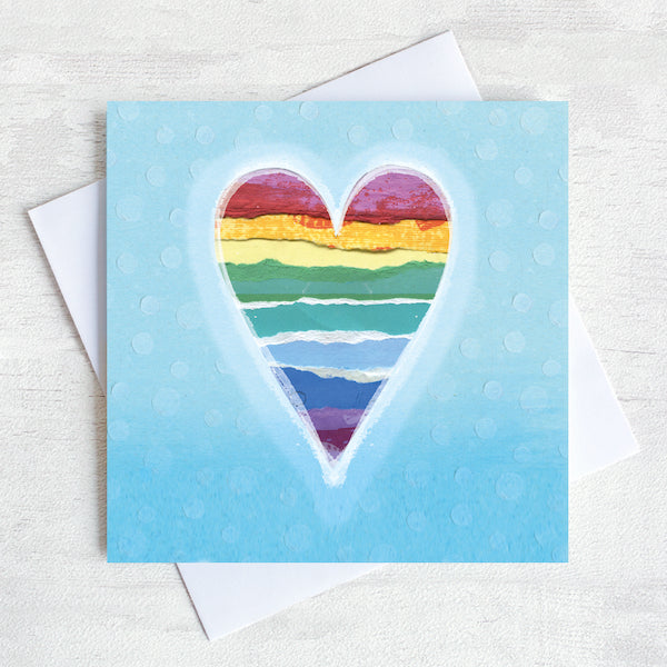 A Valentines Greetings Card featuring a rainbow striped heart  on a place blue background.