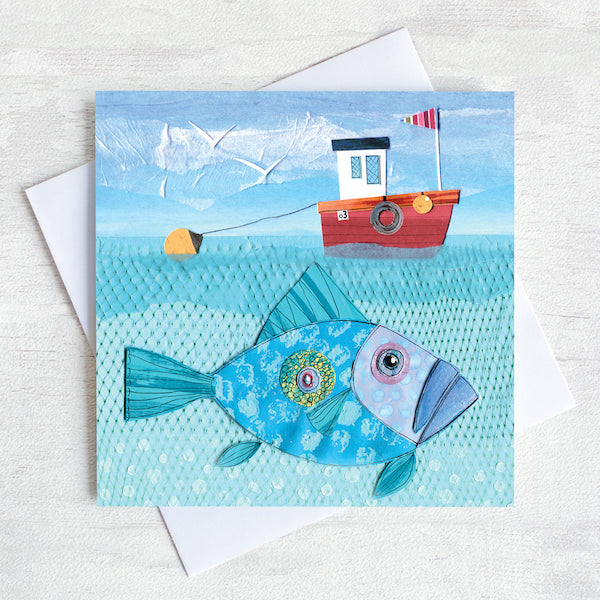 A greetings card featuring a red fishing boat with a big John Dory fish swimming underneath.