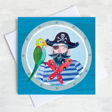 A greetings card featuring a Pirate with a green parrot on his shoulder looking through at the porthole of a ship.