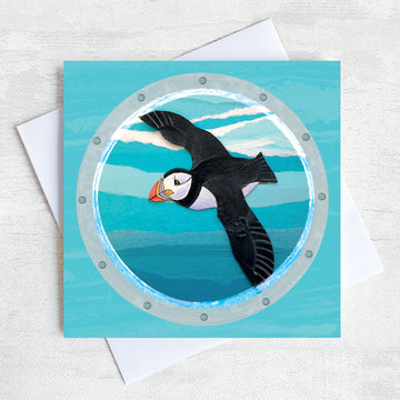 A greetings card featuring a flying puffin as viewed through a ships porthole.