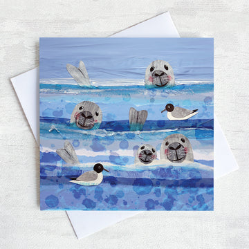 A greetings card featuring 3 seals heads bobbing in the sea amongst the black headed gulls.