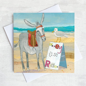 A coastal greetings card featuring a seaside donkey chatting to a seagull who is sitting on top of a sign advertising Donkey rides.