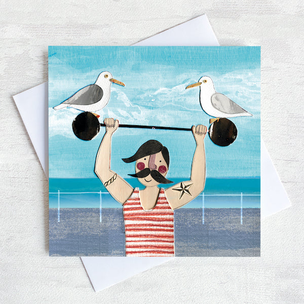 A greetings card of a dapper chap in a stripy vest lifting some weights on the sea front with two cheeky seagulls perched on top.