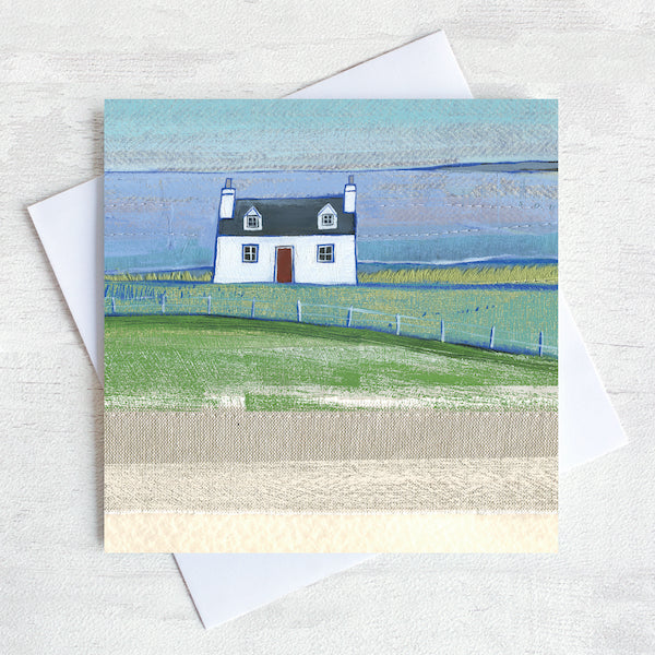A greetings card featuring a cute scottish cottage on the landscape with a view of the sea in the distance.