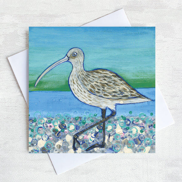 A greetings card featuring a curlew on a pebbled beach with a sea green background.