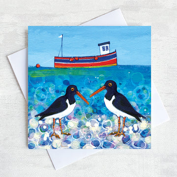 A charming greetings card from an original painting by Joanne Wishart, these quirky oystercatchers chat on a pebbled beach with a cute little fishing boat bobbing on a teal green sea.