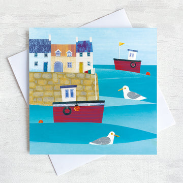 Greetings card featuring a cute harbour with red fishing boats bobbing on the sea.