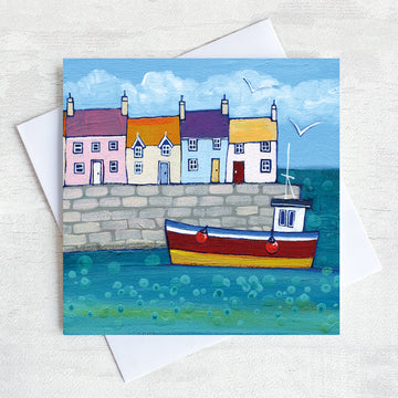 A charming coastal greetings card featuring colourful cottages on a harbour wall with a fishing boat bobbing in the water.