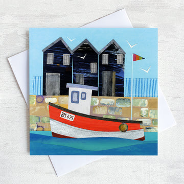 A greetings card featuring a bright red fishing boat in front of nostalgic net sheds on the harbour wall.