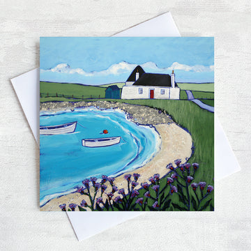 A Scottish greetings card featuring a traditional blockhouse in a sandy bay with thistles in the foreground.