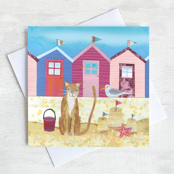 A seaside greetings card featuring a ginger cat on a beach infant of a row of colourful beach huts.