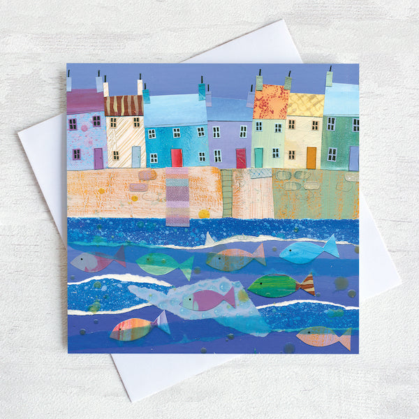 A quirky greetings card featuring a row of colourful cottages on a harbour wall with a shoal of colourful fish in the water.