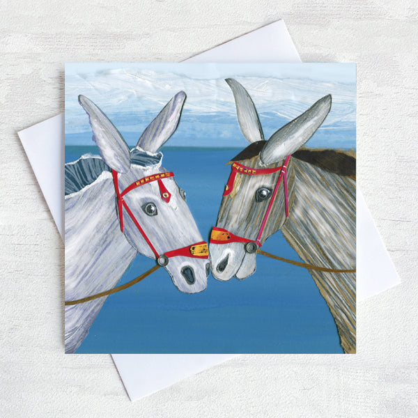 A nostalgic greetings card featuring two seaside donkeys rubbing noses on a beach.