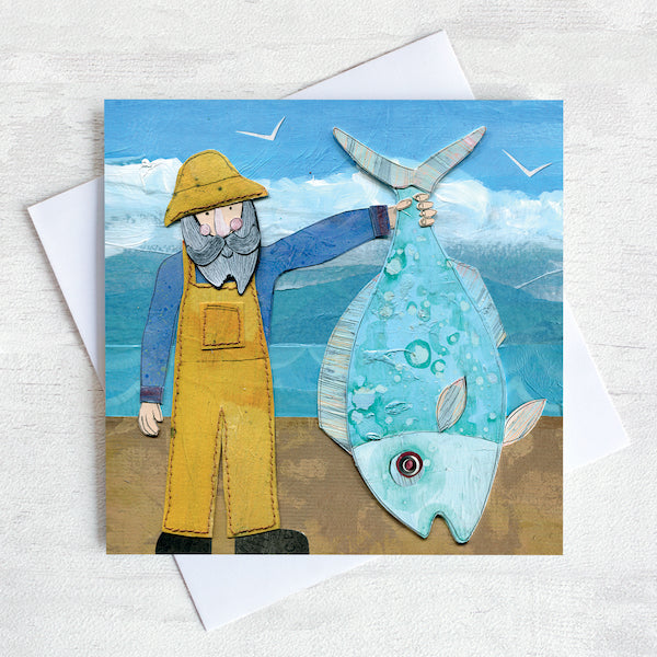 A greetings card featuring a fisherman in yellow dungarees holding up a giant fish!