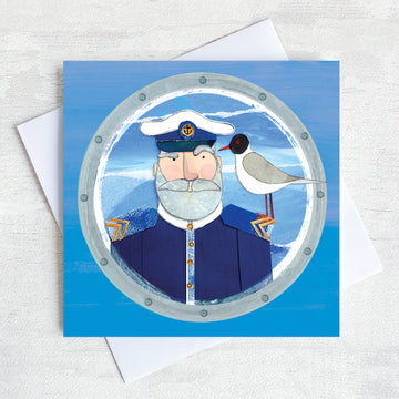 A greetings card featuring a beardy ships captain with a gull on his shoulder peeking through a porthole.