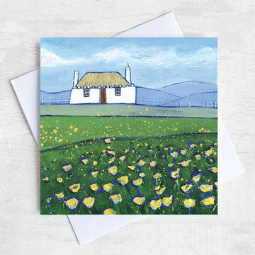 A greetings card featuring a scottish thatched cottage with a field of buttercups in the foreground.