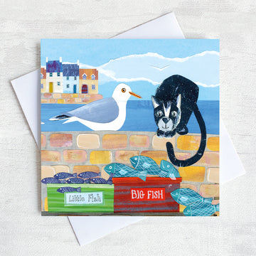 A coastal greetings card with a cute cat and seagull sitting on a harbour wall looking to eat the catch of the day