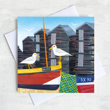 A charming seaside greetings card featuring a cute little harbour with seagulls perched on the cable boats infant of the net sheds.